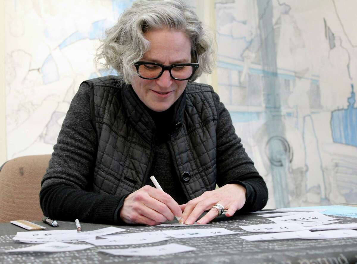 Merill Comeau, of West Concord, Mass, Weir Farm's artist in residence for February, stencils words from a personal essay she wrote about growing up in a farm house.