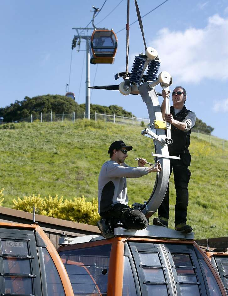 Severin Karter (left) and Martin Moser connect an arm onto the top of a cabin before it's suspended from a gondola system that will carry visitors to the Oakland Zoo's new California Trail exhibit in Oakland, Calif. on Thursday, Feb. 23, 2017. The gondola and restaurant, with a sweeping view of the Bay Area, is scheduled to open in June of this year with the entire exhibit inhabited with native California creatures slated to open in 2018.