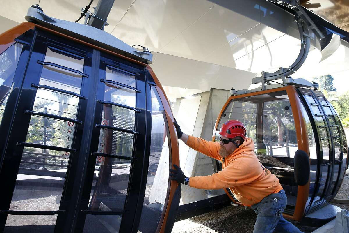 Erik Roslund pushes a cabin onto the cable of a gondola system that will carry visitors to the Oakland Zoo's new California Trail exhibit in Oakland, Calif. on Thursday, Feb. 23, 2017. The gondola and restaurant, with a sweeping view of the Bay Area, is scheduled to open in June of this year with the entire exhibit inhabited with native California creatures slated to open in 2018.