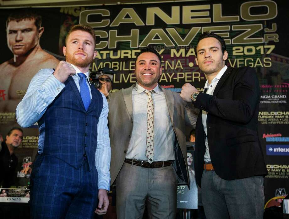 Canelo Alvarez, left, and Julio Cesar Chavez, Jr., pose for photos with Oscar de la Hoya, center, during a news conference promoting the fight between Alvarez and Chavez at Minute Maid Park on Thursday, Feb. 23, 2017, in Houston. The Mexican boxers are scheduled to fight on May 6, 2017, at T-Mobile Arena in Las Vegas. Photo: Brett Coomer, Houston Chronicle / © 2017 Houston Chronicle