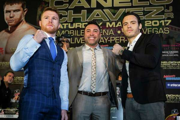 Canelo Alvarez, left, and Julio Cesar Chavez, Jr., pose for photos with Oscar de la Hoya, center, during a news conference promoting the fight between Alvarez and Chavez at Minute Maid Park on Thursday, Feb. 23, 2017, in Houston. The Mexican boxers are scheduled to fight on May 6, 2017, at T-Mobile Arena in Las Vegas.