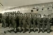 "New blue stewardess uniforms, September 30, 1939. Left to right are, Katie Wilson, Miss American Aviation for 1939, Mia J. Hill, Alga Harbaugh, Anita Loos, D. David, J. Staggers, Lois Peak, L. Canaday, M. Clark, D. Meagher, G Entrekin. It says ""The Lindbergh"" on the plane."