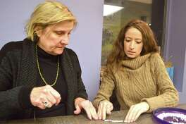 Mother-daughter team, Sue and Diana Galati, both of Westport, pitch in for charity for the bracelet-assembly project to benefit Stamford-based Pacific House, held at Art & Soul Feb. 16 in New Canaan, Conn.