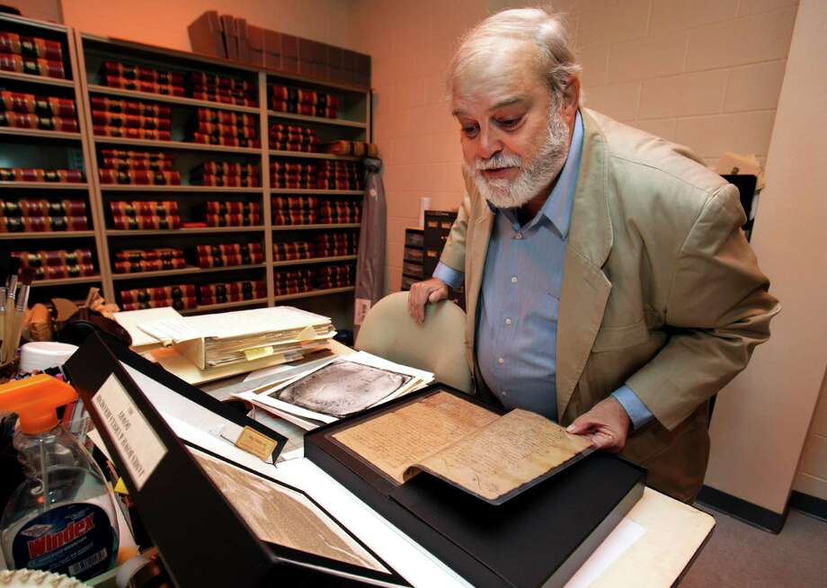 Bexar County Clerk Gerry Rickhoff reviews James Bowie documents in the vault in the Spanish Archives at the Courthouse. He and County Judge Nelson Wolff are trying to obtain artifacts regarding Bexar County colonial days from UT. A reader says they should stay in Austin. Photo: BOB OWEN /SAN ANTONIO EXPRESS-NEWS / rowen@express-news.net