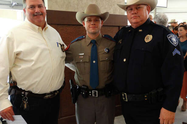 Kevin Saintes (center) is pictured with San Jacinto County Sheriff Greg Capers (left) and his father, Bernie Saintes, a patrol sergeant for Spring ISD, at Kevin's graduation from the DPS academy last year.
