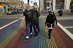 """Cleve Jones, center, hugs Gilbert Baker, left, who in 1978 created the Rainbow Flag, as they walk with Jillan Tripp, right, who helped with the creation of the flag in the Castro District in San Francisco, Calif., on Thursday, February 16, 2017. Jones, who first came to San Francisco in 1972, is one of four real-life queer liberation activists whose stories are being worked into a docu-drama around the movement on ABC called """"When We Rise."""" Cleve worked under Harvey Milk and started the AIDS quilt. He's also active in labor movement work."""
