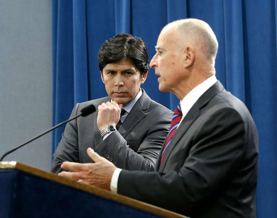 Senate President Pro Tem Kevin de Leon, D-Los Angeles listens as Calif. Gov. Jerry Brown, discusses the scaling back of a proposal to address climate change that he supported during a news conference, Wednesday, Sept. 9, 2015, in Sacramento, Calif.  Citing opposition from the oil industry,  de Leon, said he was dropping a mandate in his bill, SB350, that the state cut petroleum use by 50 percent.(AP Photo/Rich Pedroncelli) Photo: Rich Pedroncelli, AP