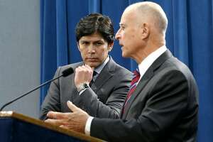 Senate President Pro Tem Kevin de Leon, D-Los Angeles listens as Calif. Gov. Jerry Brown, discusses the scaling back of a proposal to address climate change that he supported during a news conference, Wednesday, Sept. 9, 2015, in Sacramento, Calif.  Citing opposition from the oil industry,  de Leon, said he was dropping a mandate in his bill, SB350, that the state cut petroleum use by 50 percent.(AP Photo/Rich Pedroncelli)