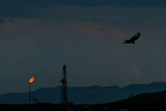 A vulture soars over an Apache Corporation flare and drilling rig north of the Davis Mountains Friday, Sept. 16, 2016 in Balmorhea, TX. The company recently announced the discovery of an estimated 15 billion barrels of oil and gas in the area and plans to drill and use hydraulic fracturing on the 350,000 acres surrounding the town. Apache has leased the mineral rights under the town and nearby state park, but has promised not to drill on or under either. While some residents worry that the drilling could affect the spring at the state park and impact tourism, others are excited for the potential economic boom the oil discovery and drilling could bring.