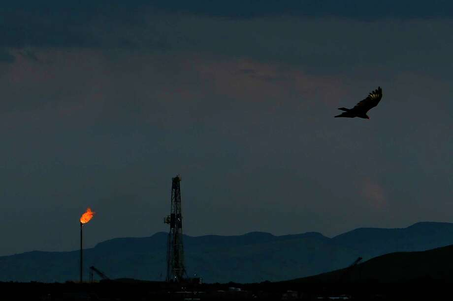 A vulture soars over an Apache Corporation flare and drilling rig north of the Davis Mountains Friday, Sept. 16, 2016 in Balmorhea, TX. The company recently announced the discovery of an estimated 15 billion barrels of oil and gas in the area and plans to drill and use hydraulic fracturing on the 350,000 acres surrounding the town. Apache has leased the mineral rights under the town and nearby state park, but has promised not to drill on or under either. While some residents worry that the drilling could affect the spring at the state park and impact tourism, others are excited for the potential economic boom the oil discovery and drilling could bring. Photo: Michael Ciaglo, Staff / © 2016  Houston Chronicle