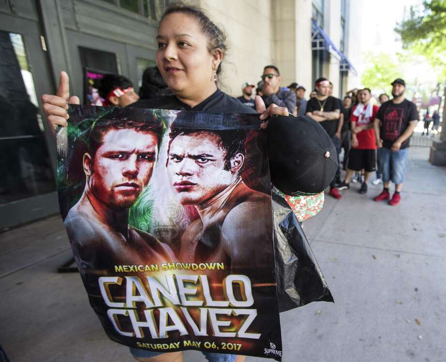 Maria Chavez holds a fight promotion sign as she waits outside Minute Maid Park to attend a press conference promoting the fight between Canelo Alvarez and Julio Cesar Chavez, Jr., on Thursday, Feb. 23, 2017, in Houston. ( Brett Coomer / Houston Chronicle ) Photo: Brett Coomer, Staff / Houston Chronicle / © 2017 Houston Chronicle