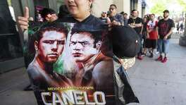 Maria Chavez holds a fight promotion sign as she waits outside Minute Maid Park to attend a press conference promoting the fight between Canelo Alvarez and Julio Cesar Chavez, Jr., on Thursday, Feb. 23, 2017, in Houston. ( Brett Coomer / Houston Chronicle )