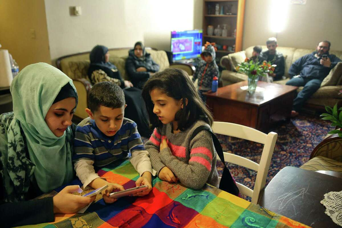 Yara Alhamdan, 17, left, brother Ahmad, 7, and friend Aya Almsetif, 7, play phone games as their families visit with each other at the Alhamdan's home in West Seattle, Feb. 14, 2017.