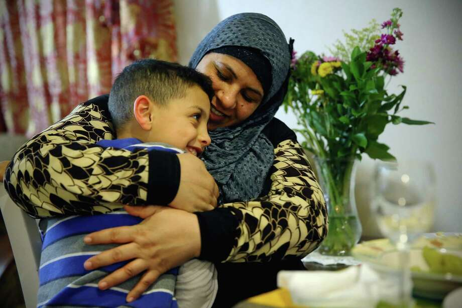 Rabah Saleh talks with her youngest son Ahmad, 7, Feb. 14, 2017. Since fleeing from Syria to the U.S. via Jordan one year ago, she has started working part time as a janitor at a local school in West Seattle. Photo: GENNA MARTIN, SEATTLEPI.COM / SEATTLEPI.COM