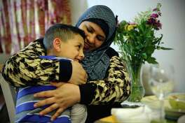 Rabah Saleh talks with her youngest son Ahmad, 7, Feb. 14, 2017. Since fleeing from Syria to the U.S. via Jordan one year ago, she has started working part time as a janitor at a local school in West Seattle.