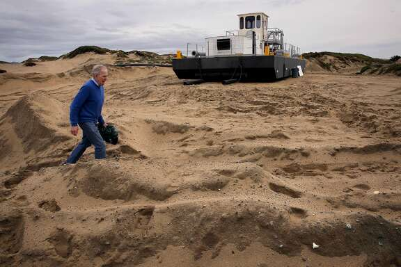 Edward Thornton, a coastal engineer with the Naval Post Graduate School walks past a dredge owned by Cemex, which removes more than 200,000 acre feet of beach sand a year along the Monterey Bay coastline in Marina, Ca., as seen on Wednesday Feb. 8, 2017,
