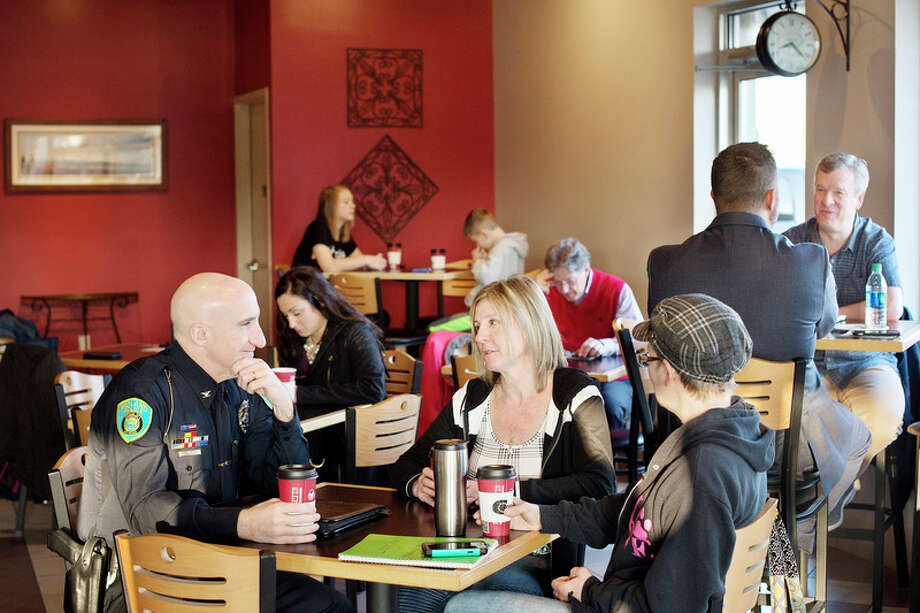 BRITTNEY LOHMILLER | blohmiller@mdn.net Midland residents Gwen Malone, center, and Stephanie Thomas, right, chat with Midland Police Chief Clifford Block at Coffee Chaos Thursday morning during the first Coffee with a Cop. / Midland Daily News