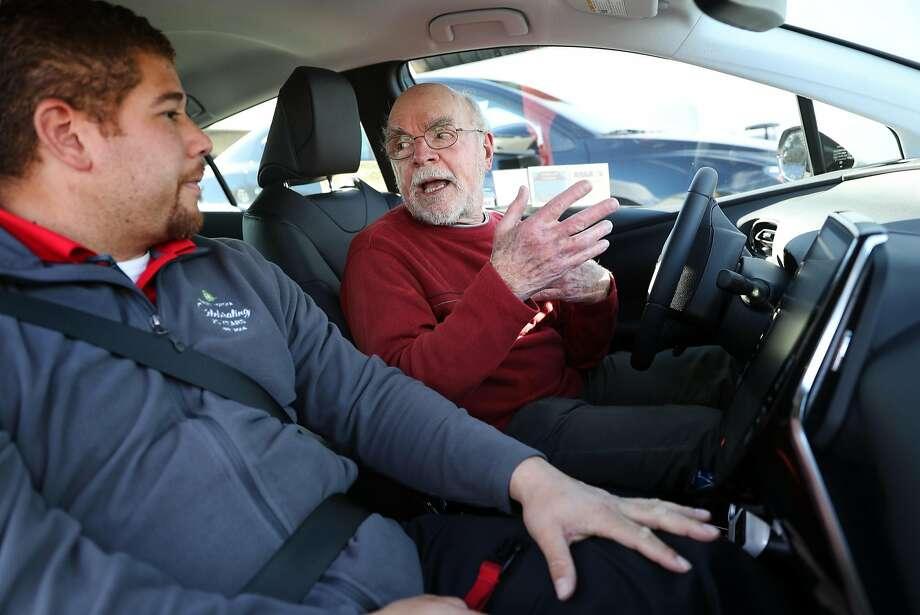 Bob Plantz (right) discusses a Toyota Prius Prime with Hansel Toyota's Cameron Hart in Petaluma. Photo: Scott Strazzante, The Chronicle