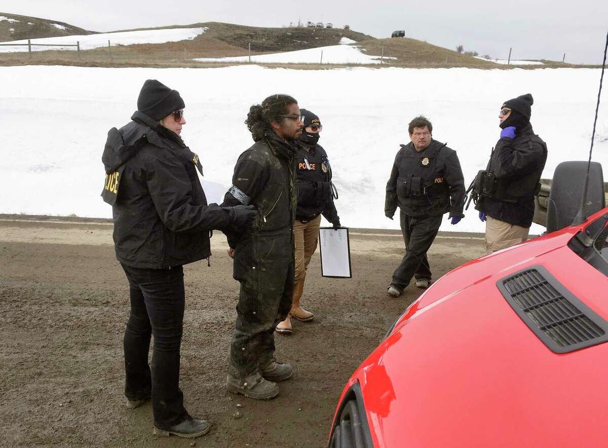 Authorities arrest one of the last remaining holdouts from the now-closed Dakota Access pipeline protest camp in southern North Dakota near Cannon Ball on Thursday, Feb. 23, 2017. Police made about several dozen arrests, and declared the camp cleared after about 3 1/2 hours. (Mike McCleary/Bismarck Tribune via AP) ORG XMIT: NDBIS502