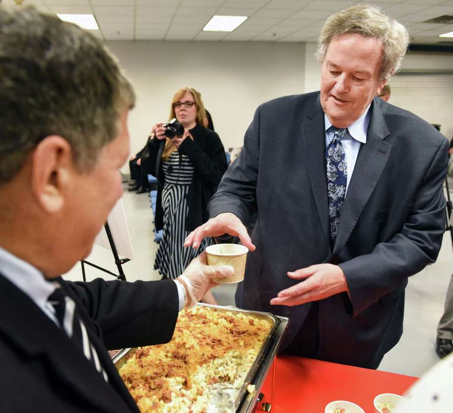 """Angelo Mazzone of Mazzone Hospitality, left, serves MAAC Commissioner Rich Ensor a dish of """"MAAC-n0Cheese"""" during an announcement of tournament details and fan activities for the 2017 MAAC MenOs and WomenOs Basketball Championships at the Times Union Center Thursday Feb. 23, 2017in Albany, NY.  (John Carl D'Annibale / Times Union) Photo: John Carl D'Annibale / 20039775A"""