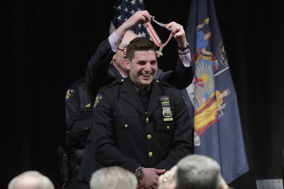 Troy Police Officer Joshua Comitale laughs as Senator Charles Schumer lifts the Congressional Badge of Bravery back off his head as it was too tight to fit over his head during an event at Hudson Valley Community College on Thursday, Feb. 23, 2017, in Troy, N.Y.  Comitale received the medal for his actions in a fatal 2015 gun battle with a carjacking suspect in Lansingburgh.  (Paul Buckowski / Times Union) Photo: PAUL BUCKOWSKI / 20039782A