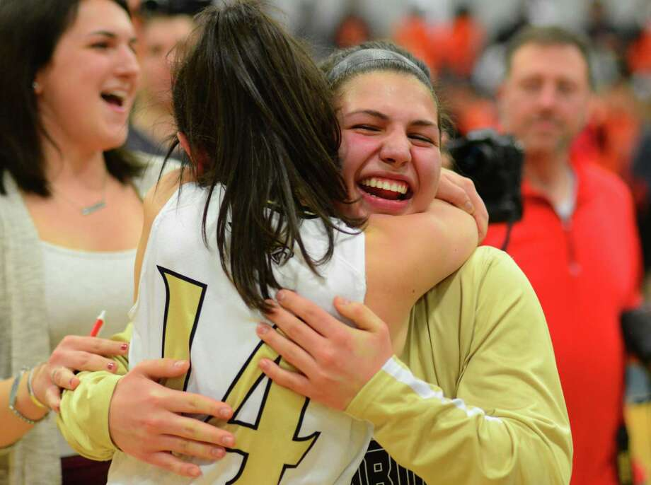 Trumbull's Gianna Ghitsa, facing camera, hugs teammate Kelly O'Leary after the team beat Stamford in FCIAC Girls Basketball Championship action in Fairfield, Conn., on Friday Feb. 23, 2017. Photo: Christian Abraham / Hearst Connecticut Media / Connecticut Post