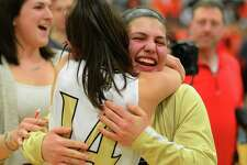 Trumbull's Gianna Ghitsa, facing camera, hugs teammate Kelly O'Leary after the team beat Stamford in FCIAC Girls Basketball Championship action in Fairfield, Conn., on Friday Feb. 23, 2017.