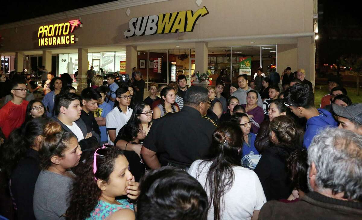 People pay their respect at a vigil held for the 18-year-pold Subway employee Javier Flores Thursday, Feb. 23, 2017, in Houston. Flores was killed when he tried to get between an armed robber and his mother, another employee.