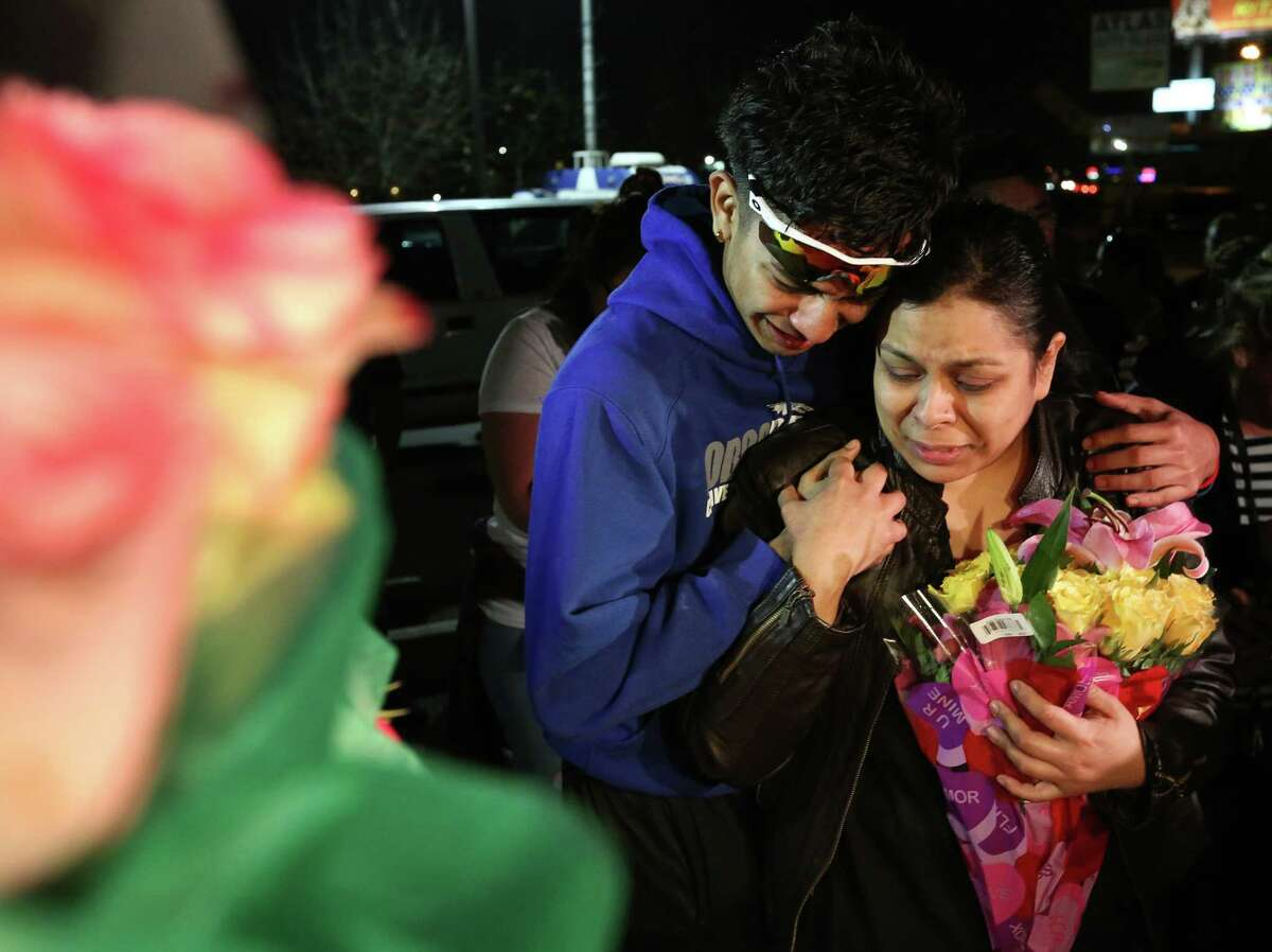 Max Vasquez, brother of 18-year-pold Subway employee Javier Flores, and his mother put flowers at the make-shift memorial at the vigil prepared for Flores Thursday, Feb. 23, 2017, in Houston. Flores tried to get between an armed robber and his mother, another employee, and was killed.