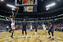 Houston Rockets guard Lou Williams (12) goes to the basket between New Orleans Pelicans forward Omri Casspi (18) and forward DeMarcus Cousins (0) in the second half of an NBA basketball game in New Orleans, Thursday, Feb. 23, 2017. The Rockets won 129-99. (AP Photo/Gerald Herbert)