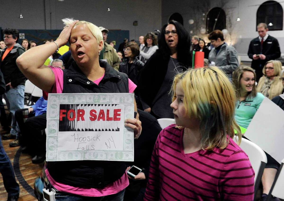 Hoosick Falls resident Laura Peabody ,left, and her daughter Ashlynn Sagendorf age 10 react after Mayor David Borge postponed a meeting during a news conference at the Hoosick Falls Armory concerning a settlement agreement between the village of Hoosick Falls and Saint-Gobain Performance Plastics and Honeywell of the handling of PFOA contamination in the villages drinking water in Hoosick Falls, N.Y., on Thursday, Feb. 23, 2017, (Hans Pennink / Special to the Times Union) ORG XMIT: HP104