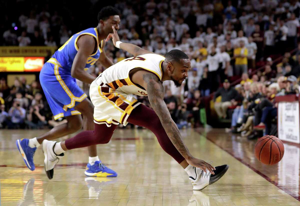 Arizona State guard Torian Graham (4) and UCLA guard Isaac Hamilton chase down a loose ball during the first half of an NCAA college basketball game, Thursday, Feb. 23, 2017, in Tempe, Ariz. (AP Photo/Matt York) ORG XMIT: AZMY105