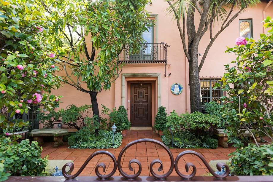 A tile courtyard receives shade from mature trees in front of the Mediterranean home in Piedmont. Photo: Liz Rusby / The Grubb Co.