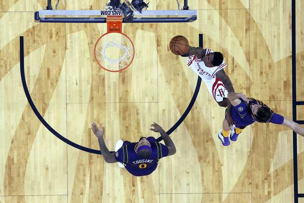 Houston Rockets guard Lou Williams (12) goes to the basket against New Orleans Pelicans forwards DeMarcus Cousins (0) and Omri Casspi (18) during the second half of an NBA basketball game in New Orleans, Thursday, Feb. 23, 2017. The Rockets won 129-99. (AP Photo/Gerald Herbert)