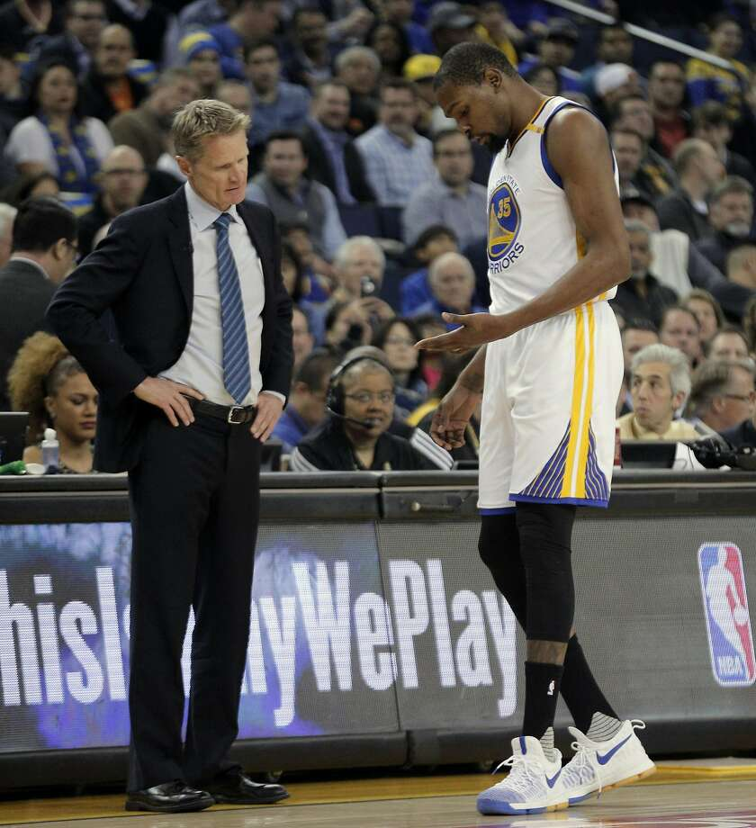 Warriors head coach Steve Kerr checks out Kevin Durant's (35) hand after he landed awkwardly on it in the first half as the Golden State Warriors played the Los Angeles Clippers at Oracle Arena in Oakland, Calif., on Thursday, February 23, 2017. Photo: Carlos Avila Gonzalez, The Chronicle