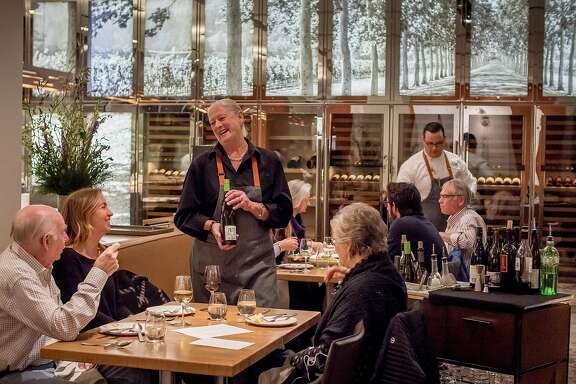 Server Lillian Wiggins offers wine to diners at CIA at Copia in Napa, Calif. on February 23rd, 2017.