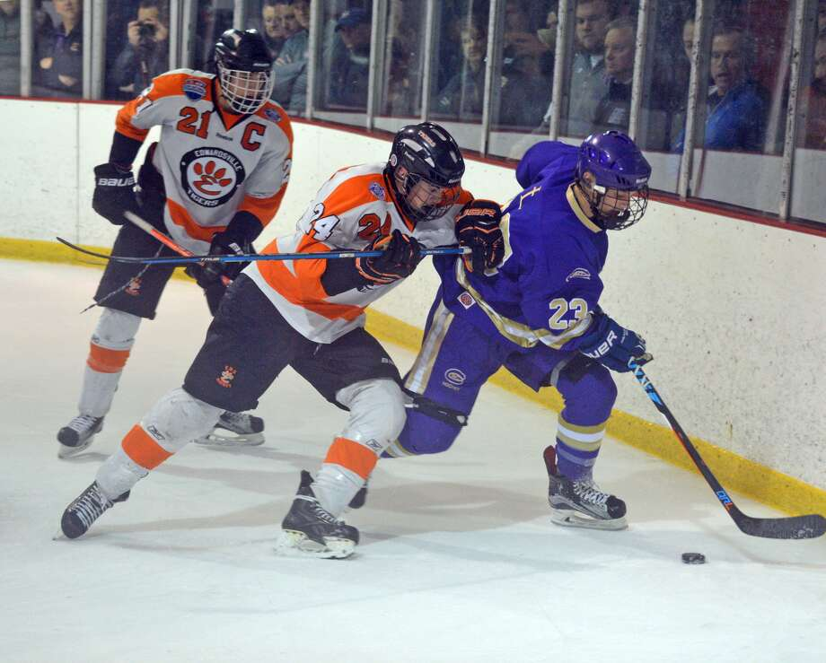 Edwardsville's James Akeman, middle, battles CBC's Michael Deeba for the puck during Thursday's game at the Hardee's Ice Complex in Chesterfield, Mo.