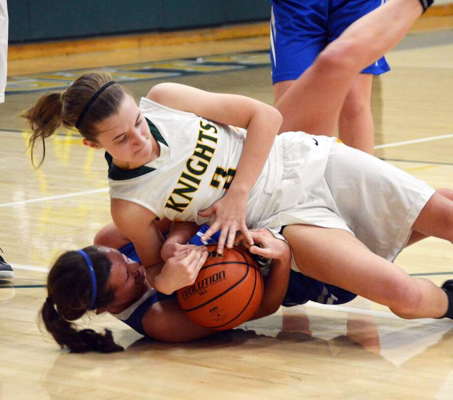 Metro-East Lutheran guard Sami Kasting, top, tries to wrestle the ball away from an Alton Marquette player during the second quarter of a regular season game at Thomas Hooks Gym.