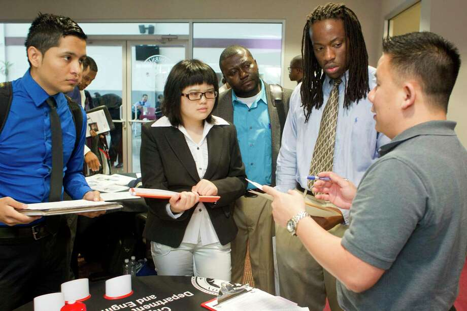 """Bach Le, right, a senior human resources specialist with the City of Houston, talks with a group of Texas Southern University Students including Izogbu Wells, 22, second right, a civil engineering student, during the Texas Southern University Maritime, Transportation and Engineering Career Fair held on campus Wednesday, April 23, 2014, in Houston. """"I'm looking for an internship,"""" Wells said, who plans on graduating in December 2015. """"I came to talk to people and broaden my horizons to what is out there."""" ( Johnny Hanson / Houston Chronicle ) Photo: Johnny Hanson / © 2014  Houston Chronicle"""