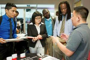 """Bach Le, right, a senior human resources specialist with the City of Houston, talks with a group of Texas Southern University Students including Izogbu Wells, 22, second right, a civil engineering student, during the Texas Southern University Maritime, Transportation and Engineering Career Fair held on campus Wednesday, April 23, 2014, in Houston. """"I'm looking for an internship,"""" Wells said, who plans on graduating in December 2015. """"I came to talk to people and broaden my horizons to what is out there."""" ( Johnny Hanson / Houston Chronicle )"""