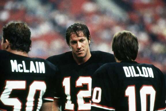06/10/1984 - Houston Gamblers quarterback Jim Kelly (12) with teammates Kevin McLain (50) and Todd Dillon (10) on sideline