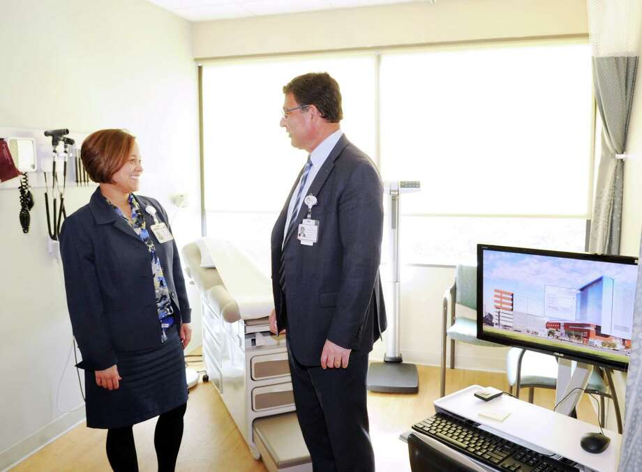 At left, Lisette Torres, Stamford Medical Group administrator, left, speaks with Dr. Rod Acosta, president and chief executive officer of Stamford Medical Group in a patient examination room in the Walk In Center at the Stamford Health Medical Group, Stamford Hospital's outpatient center in Stamford, Conn., Tuesday, Feb. 21, 2017. The facility located at 292 Long Ridge Road houses doctors focusing on primary care, cardiology, endocrinology, neurology, obstetrics, gynecology and orthopedics, as well as diagnostic imaging labs and a walk-in center. Photo: Bob Luckey Jr. / Hearst Connecticut Media / Greenwich Time