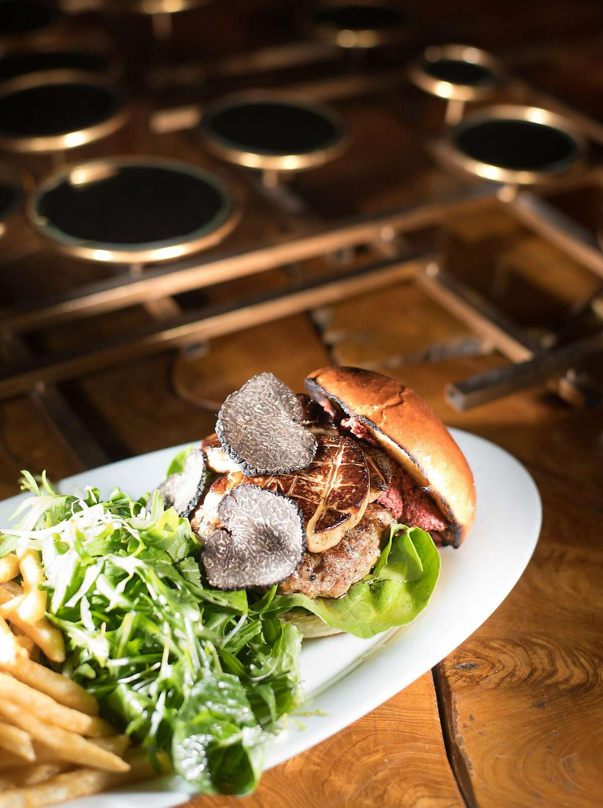 A Sonoma Duck Burger with foie gras rests on a table at Lucia on Thursday, February 16, 2017, in Carmel Highlands, Calif.