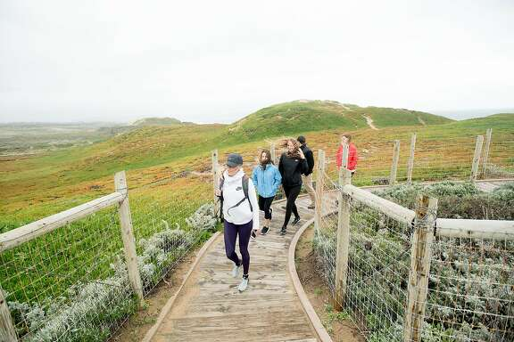 Visitors walk a path in Fort Ord Dunes State Park on Saturday, Feb. 18, 2017, in Marina, Calif.