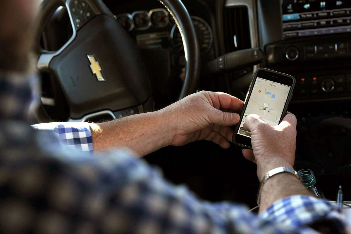 Tim Greer of Lenorah Operators shows off technology on his smartphone that allows him to track his fleet vehicles in real time. But some aspects of the oil and gas business still rely heavily on old-fashioned paper and pencil bookkeeping.