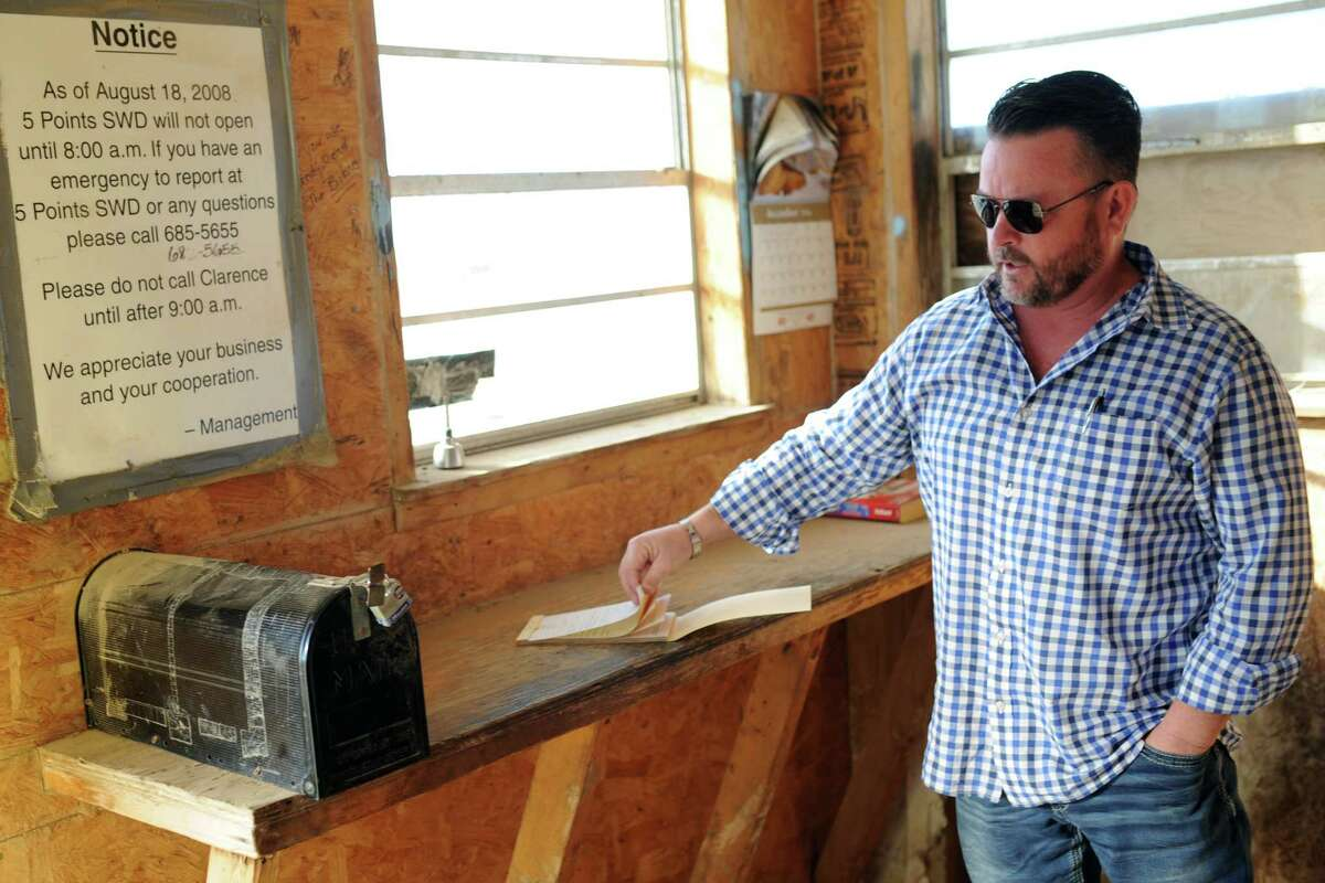 Tim Greer, of Lenorah Operators, points out a copy book and a mailbox where drivers record and file their stops at a wastewater recycling well located on Highway 158 south of Midland, Wednesday, Feb. 1, 2017. Despite advances in technology, some aspects of the oil and gas business still rely heavily on old-fashioned paper and pencil book-keeping methods. James Durbin/Reporter-Telegram