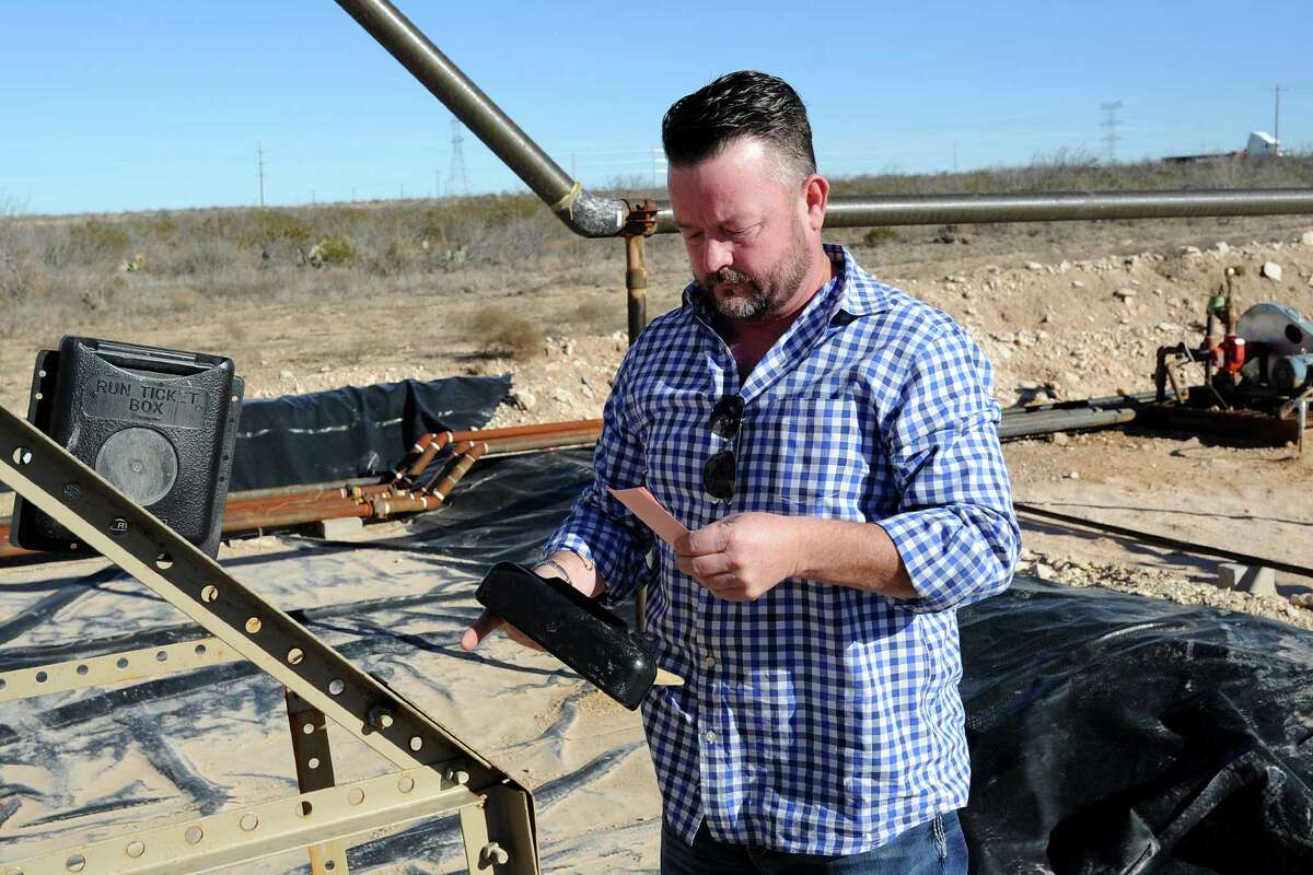 Tim Greer points out a copy book and a mailbox where drivers record and file their stops on an oil and gas lease near Midland.