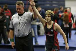 In this Feb. 18, 2017 photo, Euless Trinity's Mack Beggs is announced as the winner of a semifinal match after Beggs pinned Grand Prairie's Kailyn Clay during the finals of the UIL Region 2-6A wrestling tournament at Allen High School in Allen, Texas.   Beggs, who is transgender, is transitioning from female to male, won the girls regional championship after a female opponent forfeited the match. (Nathan Hunsinger/The Dallas Morning News via AP)