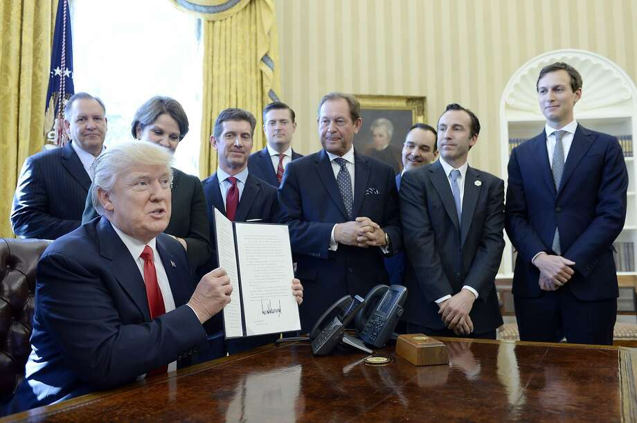 President Donald Trump flanked by business leaders signs executive order establishing regulatory reform officers and task forces in US agencies in the Oval Office of the White House on February 24, 2017 in Washington, DC. Earlier in the day, Trump stated he would cut 75 percent of regulations. Photo: Pool, Getty Images
