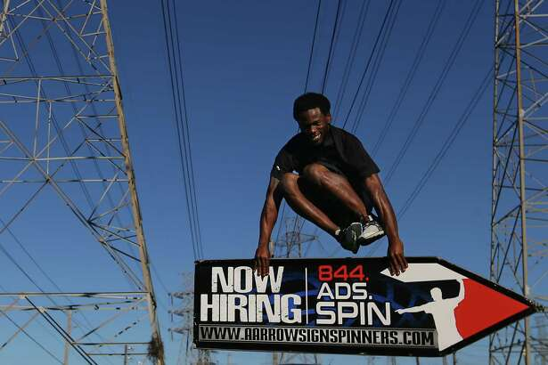 Calvin White jumps over his sign as he demonstrates his moves at the Danny Jackson Family Bark Park, Tuesday, Feb. 21, 2017, in Houston. The Houston spinners are on their way to the 2017 AArrow Sign Spinners World Championship in Las Vegas this weekend.